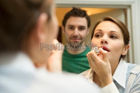 young woman applying lipstick in bathroom