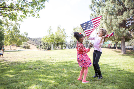 girls with american flags playing in
