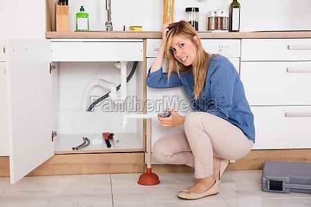 sfrustrowana kobieta o problem zlew kuchenny
