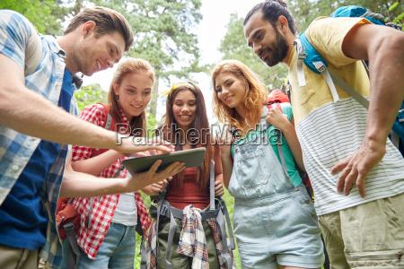 szczesliwy przyjaciele z plecaki i tablet