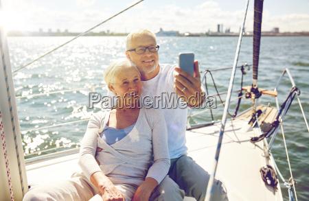 seniorzy ze smartfonem biorac selfie na