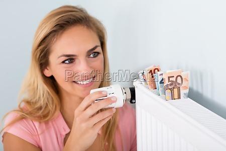 kobieta regulacja termostatu z notatek bankowych