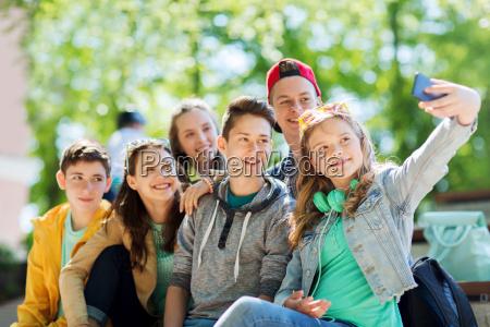 szczesliwy nastoletnich uczniow biorac selfie przez