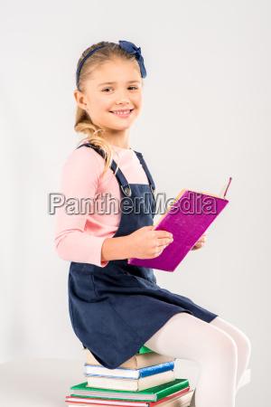 usmiechnieta uczennica trzyma ksiazke