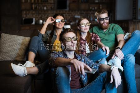mlodzi przyjaciele w okularach 3d ogladanie