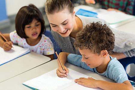 nauczyciel pomaga szkoldzieciom pisac na ksiazce
