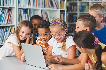 usmiechnieta szkola dzieci patrzac na laptopa