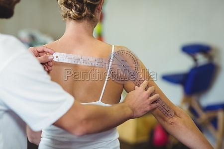 male therapist measuring female patient back