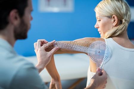 male therapist measuring female patient shoulder