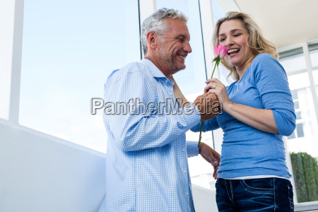 happy man giving rose to woman