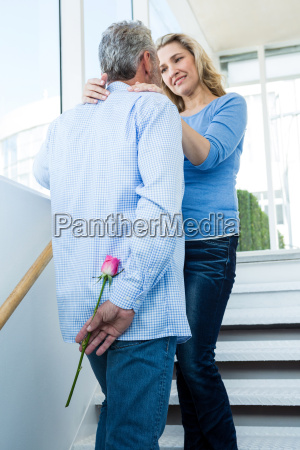 man hiding rose from woman