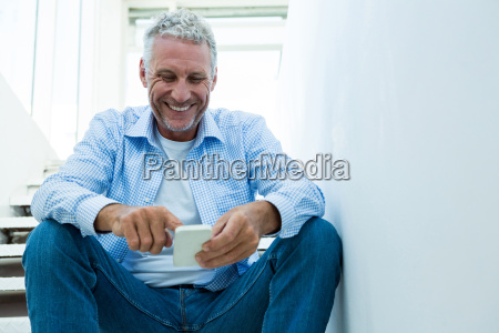 happy mature man using smartphone at
