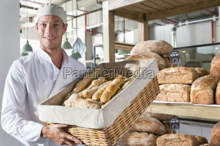 portrait of baker with fresh rolls