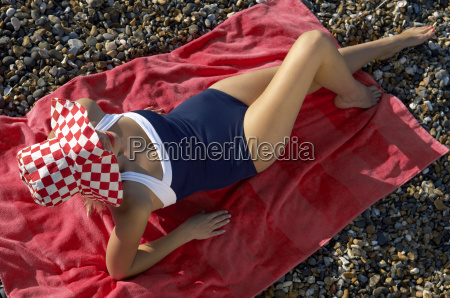 woman sitting on towel at beach