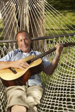 man in hammock with guitar