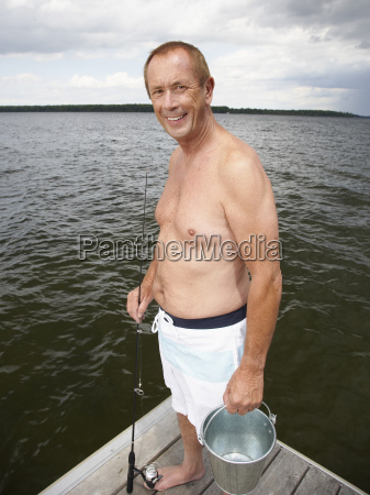 man on dock with fishing gear