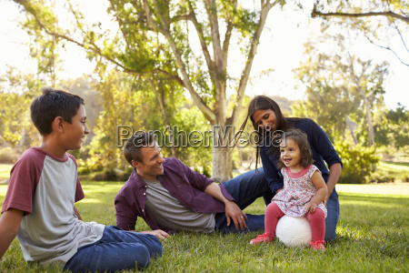 young mixed race family relaxing with