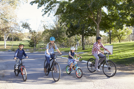 young white family cycling together through