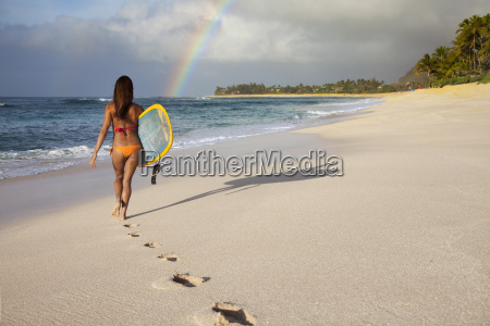 a surfer girl walking on the