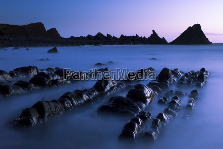 waves moving over jagged rocks at
