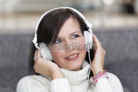 portret usmiechnieta kobieta z bialego sluchawki