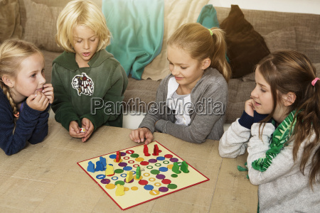 czworo dzieci gra chinczyk w salonie