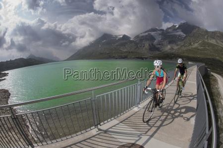 szwajcaria engadin dwoch rowerzystow na kladce