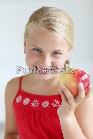 smiling blond girl holding an apple