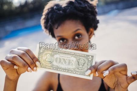 kobieta pokazujaca jeden banknot banknotu zblizenie