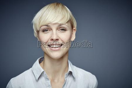 portret usmiechnietej blond kobiety przed szarym