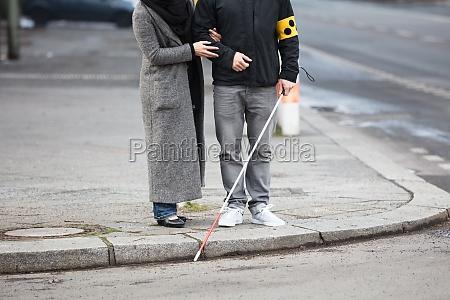 kobieta z slepym czlowiekiem na ulicy