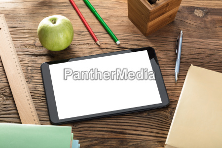 apple with digital tablet on wooden
