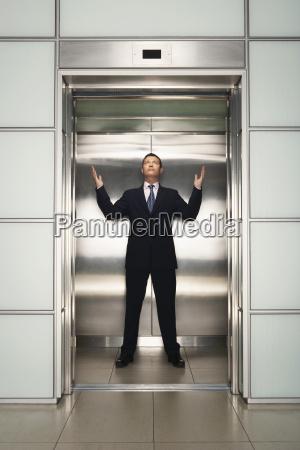 biznesmen z podniesionymi ramionami stojacy w