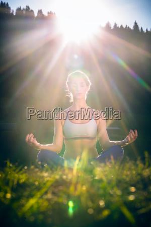 kobieta robi joge w zachodzie slonca