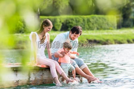 szczesliwa rodzina siedzi na molo na