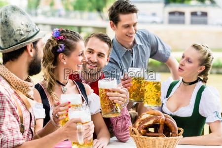przyjaciele w bawarskim ogrodku piwnym pije