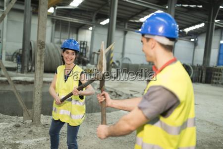 pracownicy fabryki playfighting z lopatami