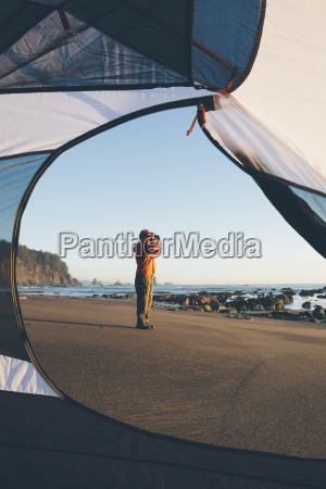 man framed by camping tent standing