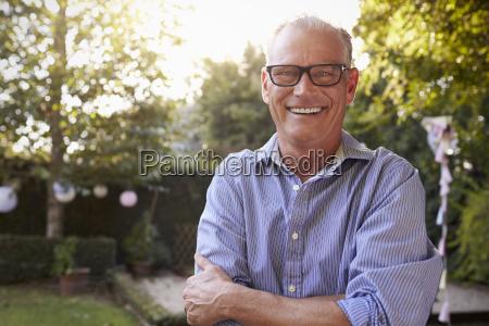 portret dojrzalego czlowieka w podworku ogrod