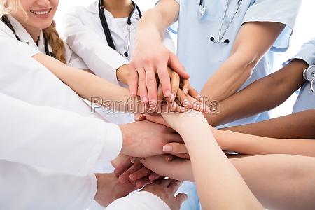 grupa lekarzy ukladania ich rece