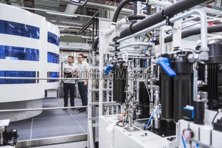 dwa mezczyzna patrzeje maszyne w fabryki