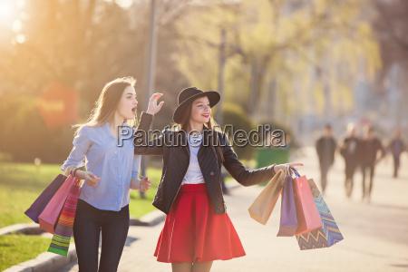 dwie dziewczyny spaceru ze sklepami na