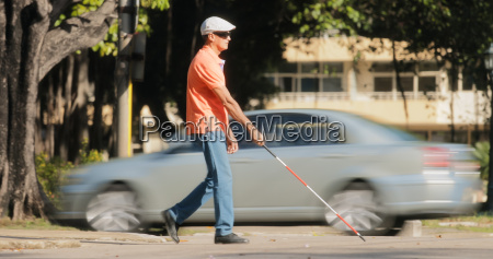 Slepy czlowiek przekraczania drogi z samochodow