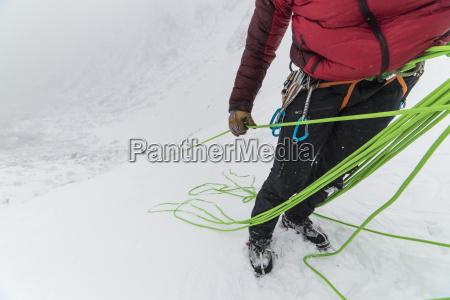 ice climber belaying partner up to