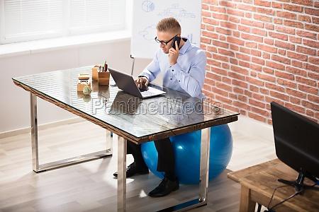businessman sitting on fitness ball working