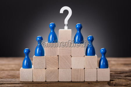 pawn figurines on wooden blocks with
