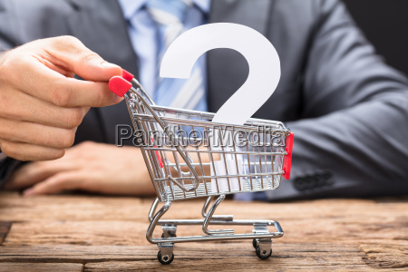 businessman pushing question mark in shopping