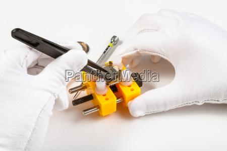 zastepujac baterie w zegarku kwarcowym pincetami