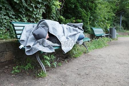 bezdomny czlowiek spi na lawce