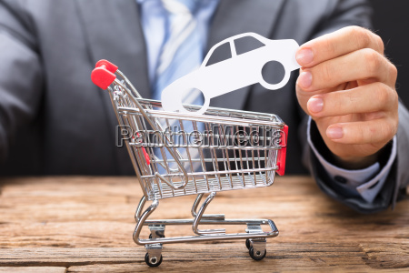 businessman holding paper car over shopping
